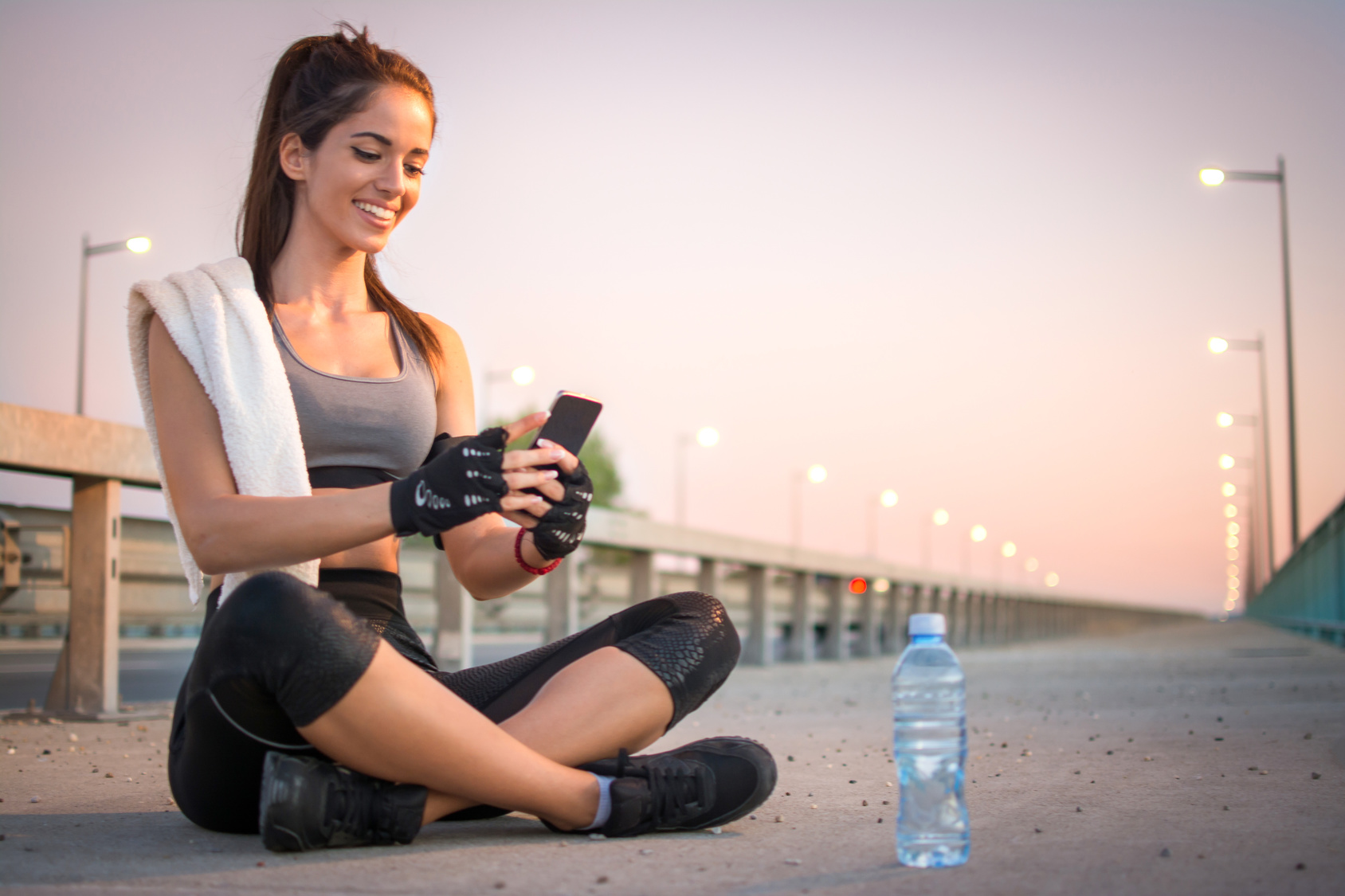 Beautiful Smiling Sportswoman Taking A Break After Workout And Using Phone Outdoors.